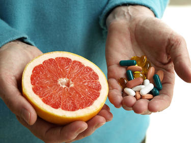 Doctor holding an orange and some vitamins